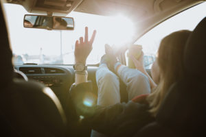Woman is using V sign gesture inside of car at sunset